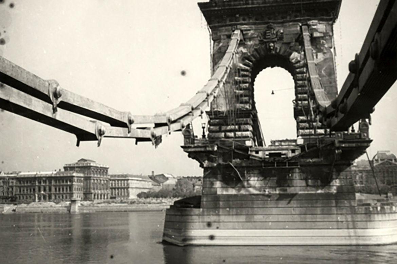 A Lánchíd roncsai Budáról fotózva, a háttérben a Magyar Tudományos Akadémia épülete és a Gresham palota. Forrás: Nullaév / MNM Fotótár
